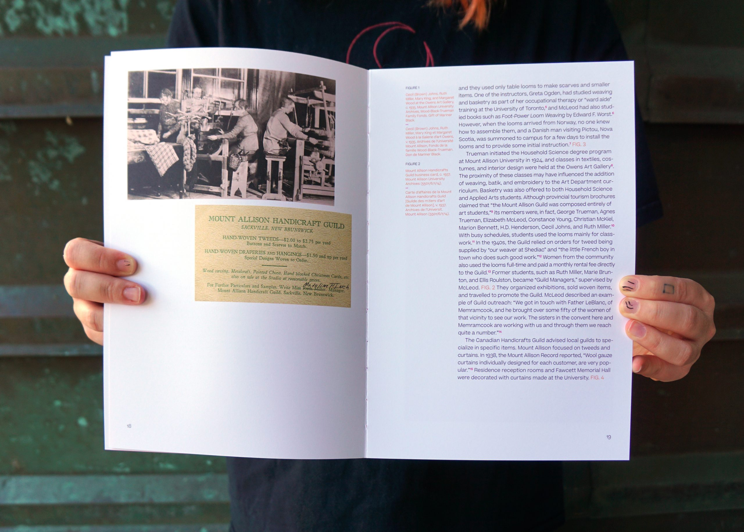 """A pair of hands holds open a book with white pages. On the left, a sepia-toned photo shows women working at looms above an image of a cream business card that reads """"Mount Allison Handicrafts Guild"""". On the right, are three paragraphs of an essay and image captions."""