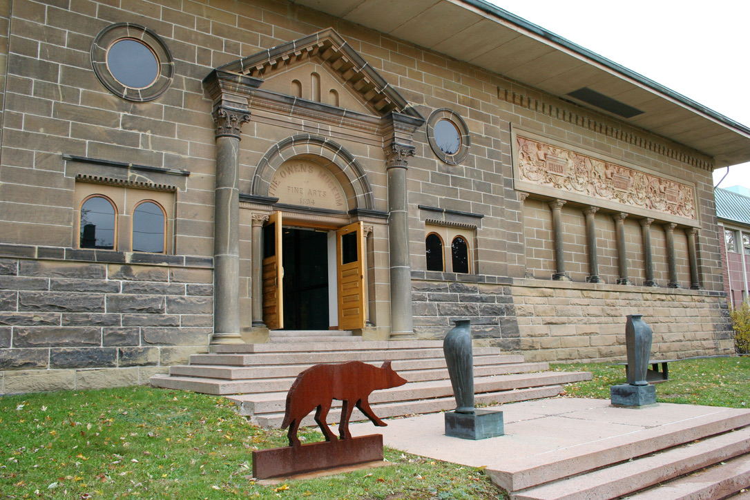 """A life-sized, rust-coloured wolf, a pair of steel split urns, and low-lying bench are installed across the wide front steps leading to the entrance of a classically inspired stone building. Above the door, carved in stone, are the words """"Owens Museum of Fine Arts, 1894""""."""