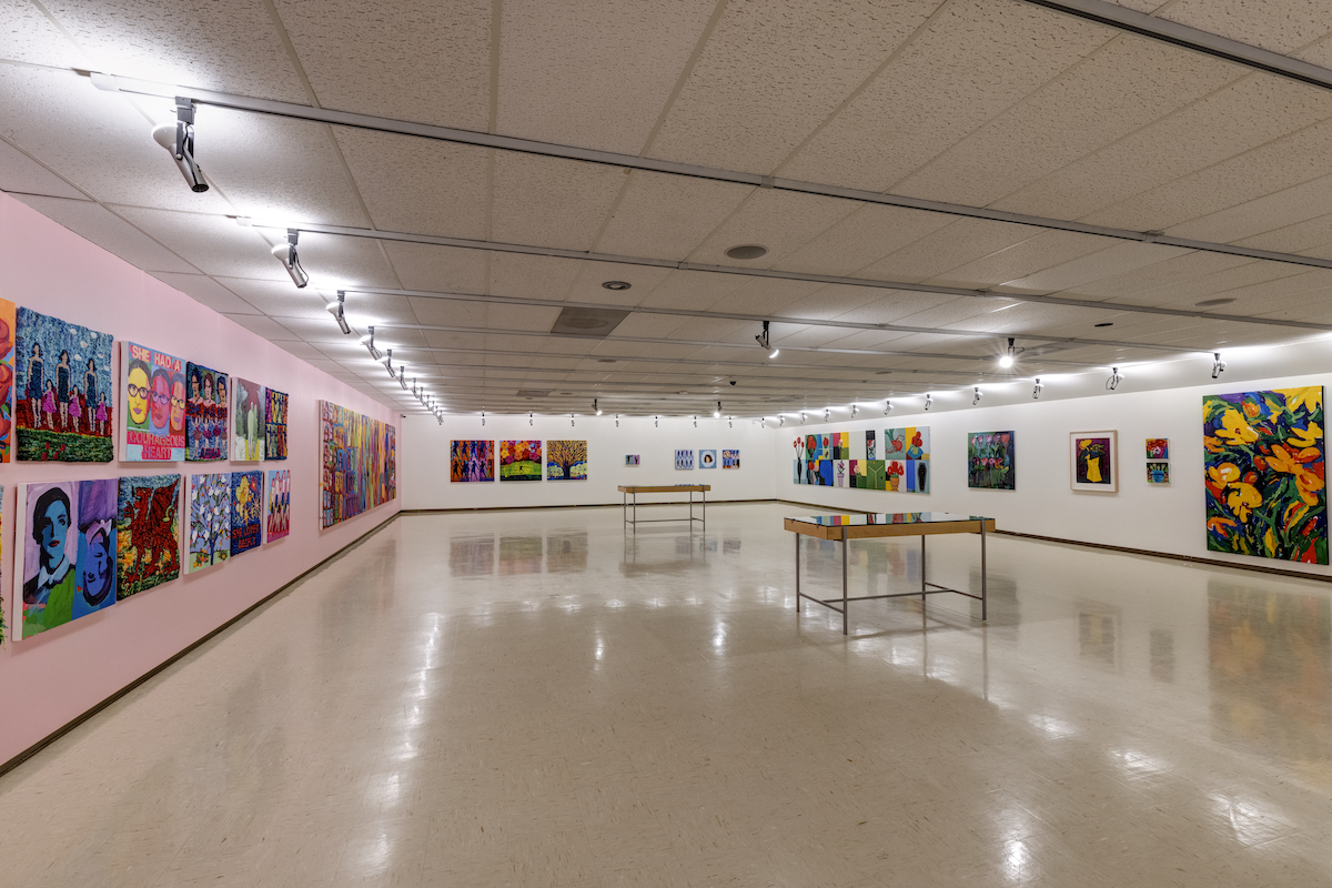 In a gallery, brightly coloured rug hookings and paintings of a female figure, trees and flowers. One wall is painted millennial pink. In the centre of the room are two display cases.
