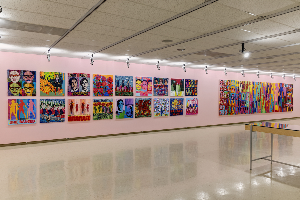 Two rows of colourful hooked rugs and paintings hang on a pink wall. To the right paintings depicting silhouettes of a woman's face and body are repeated, overlapping in several sizes and colours.