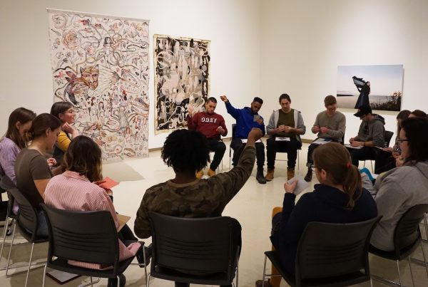 In a gallery, a group of university students sit on chairs in a semi-circle in front of a large, intricate embroidery that hangs from the ceiling in front of them. The students are focused on small stitching projects. They hold squares of felt in their hands. Some extend their arms while pulling stitches, others work on threading their needles.