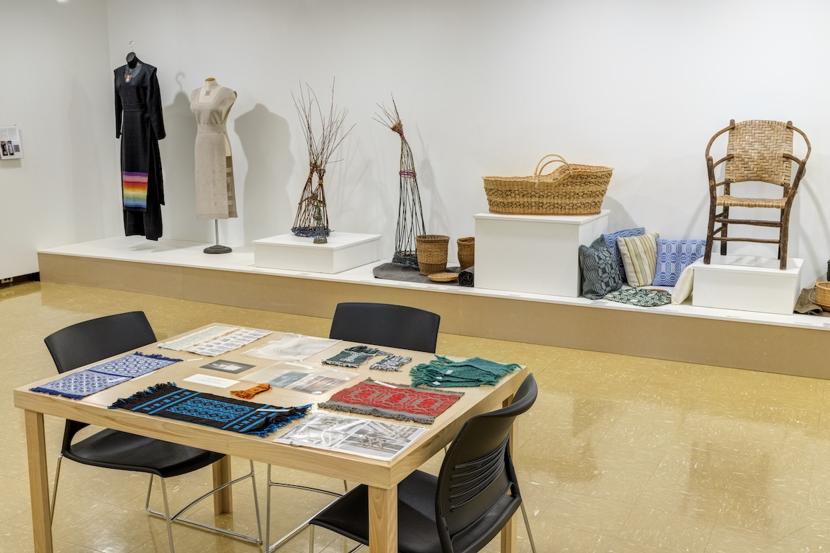 A white walled gallery is filled with examples of weaving and basketry on the walls, shelves and platforms.