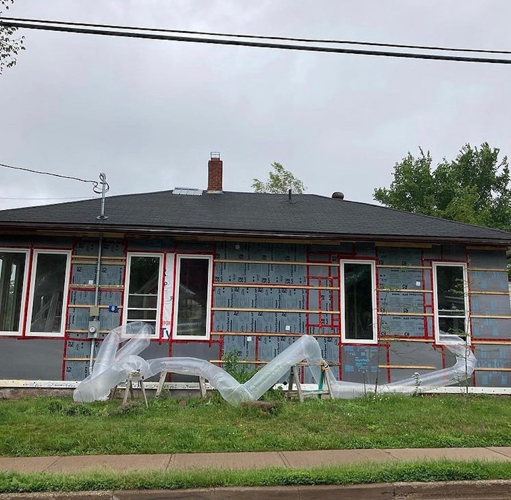 Inflated transparent plastic tubes spill out the windows of a one-storey house. Sawhorses hold up parts of the tube as it zig-zags across the lawn. The house is under construction, with no siding to reveal the insulation.