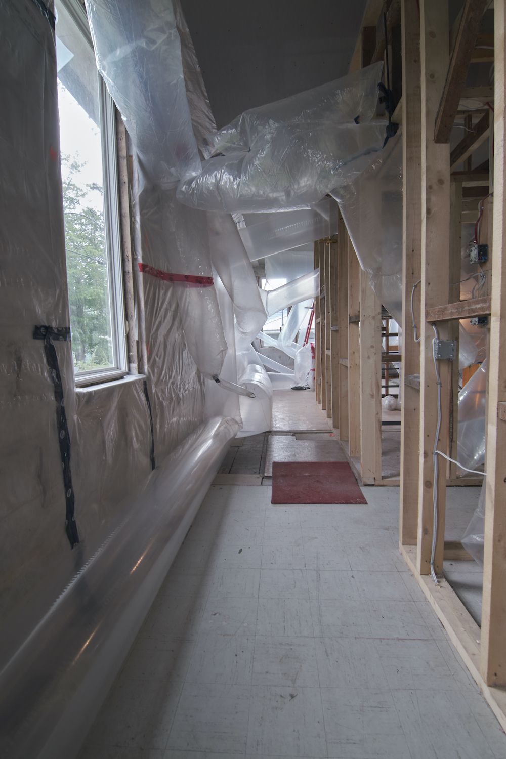 Looking down a hallway, inflated transparent plastic tubes jut out from bare stud walls. Daylight shines in the windows on the left hand side of the hall.