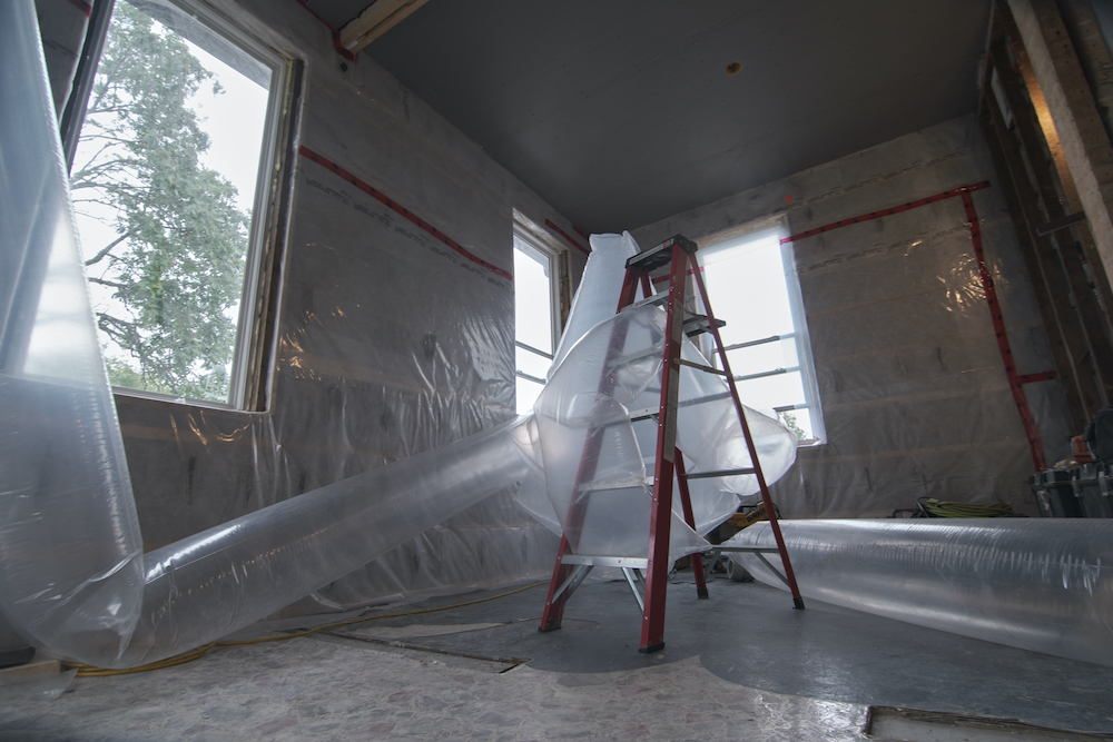 Tubes of transparent fabric wrap around a red ladder, filling the room of a house under construction. Red tuck tape holds plastic that cover the walls.