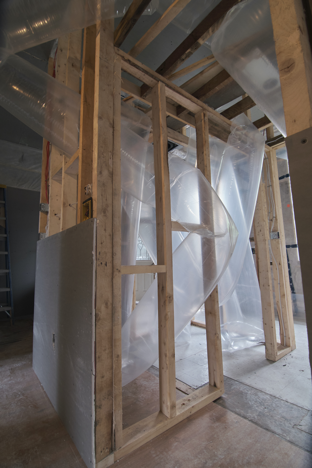 Inflated tubes of transparent plastic are woven through the bare stud walls of an under-construction house.