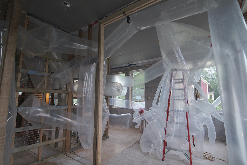 Inside an under construction house, long transparent plastic tubes and amorphous forms wrap around a ladder and weave through the open stud walls.