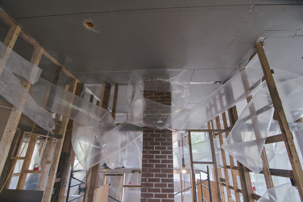 Wrapping around a red brick chimney and weaving through bare stud walls, inflated tubes of transparent plastic fill the space of an under-construction house.