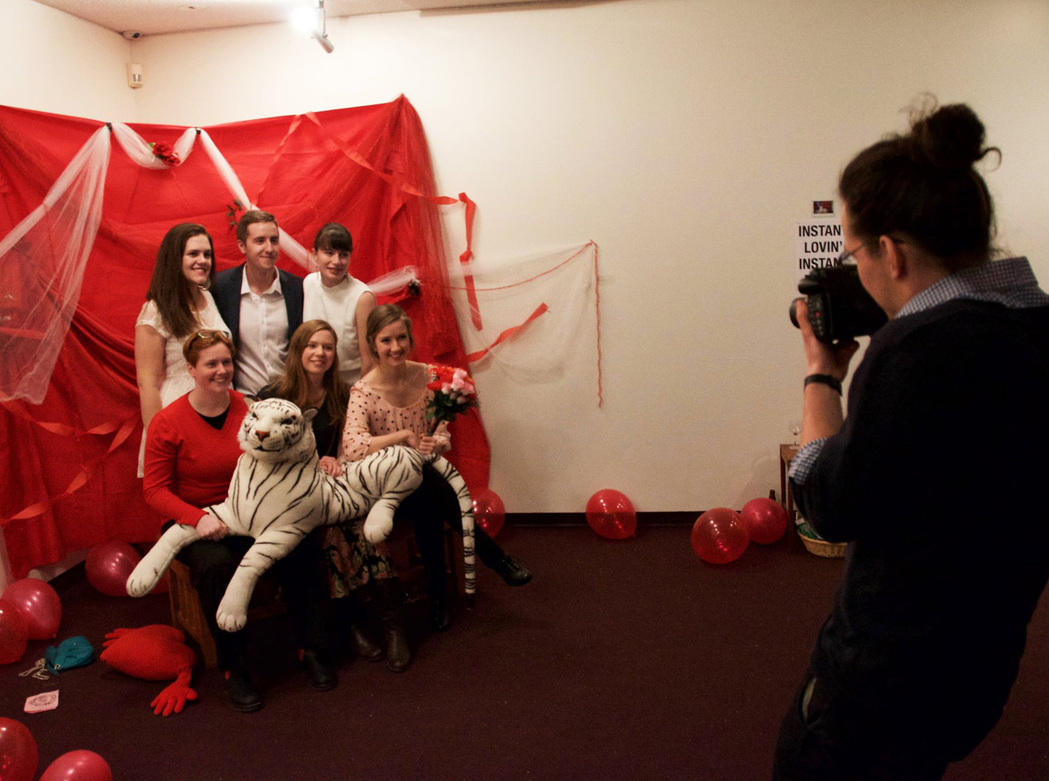 In the lobby of the Owens Art Gallery, a group of smiling adults gather together in front of a backdrop decorated with red fabric, streamers, balloons, and plastic flowers. Three adults stand while three sit in front, holding a large white stuffed tiger. A photographer stands before them, ready to capture their photo using a Polaroid camera.