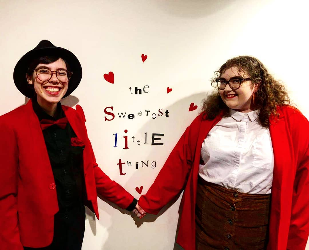 """Two adults, both wearing red jackets, hold hands and smile in front of wall text that reads """"The Sweetest Little Thing"""" written in several different fonts."""