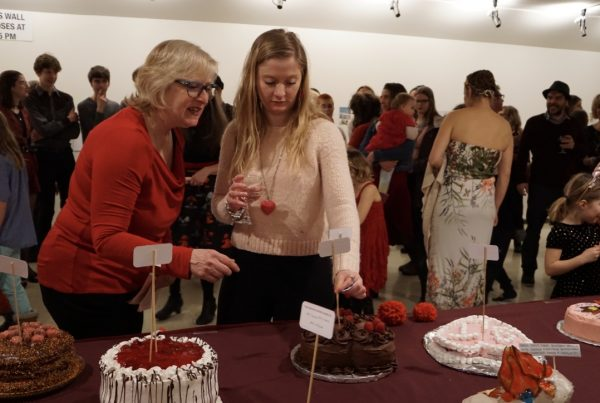Two adults stand over a long table displaying several elaborately decorated cakes on a red table cloth. They put a paper flag on a dowel in one of the cakes, while a crowd of people of all ages mingle together in the gallery space behind them.