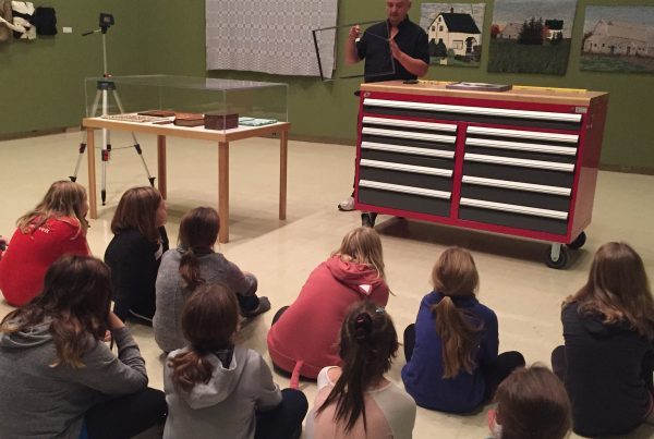 In a gallery an adult stands addressing a group of children sitting on the floor. The adult holds an empty picture frame in their hands, while standing beside a large mobile work bench.