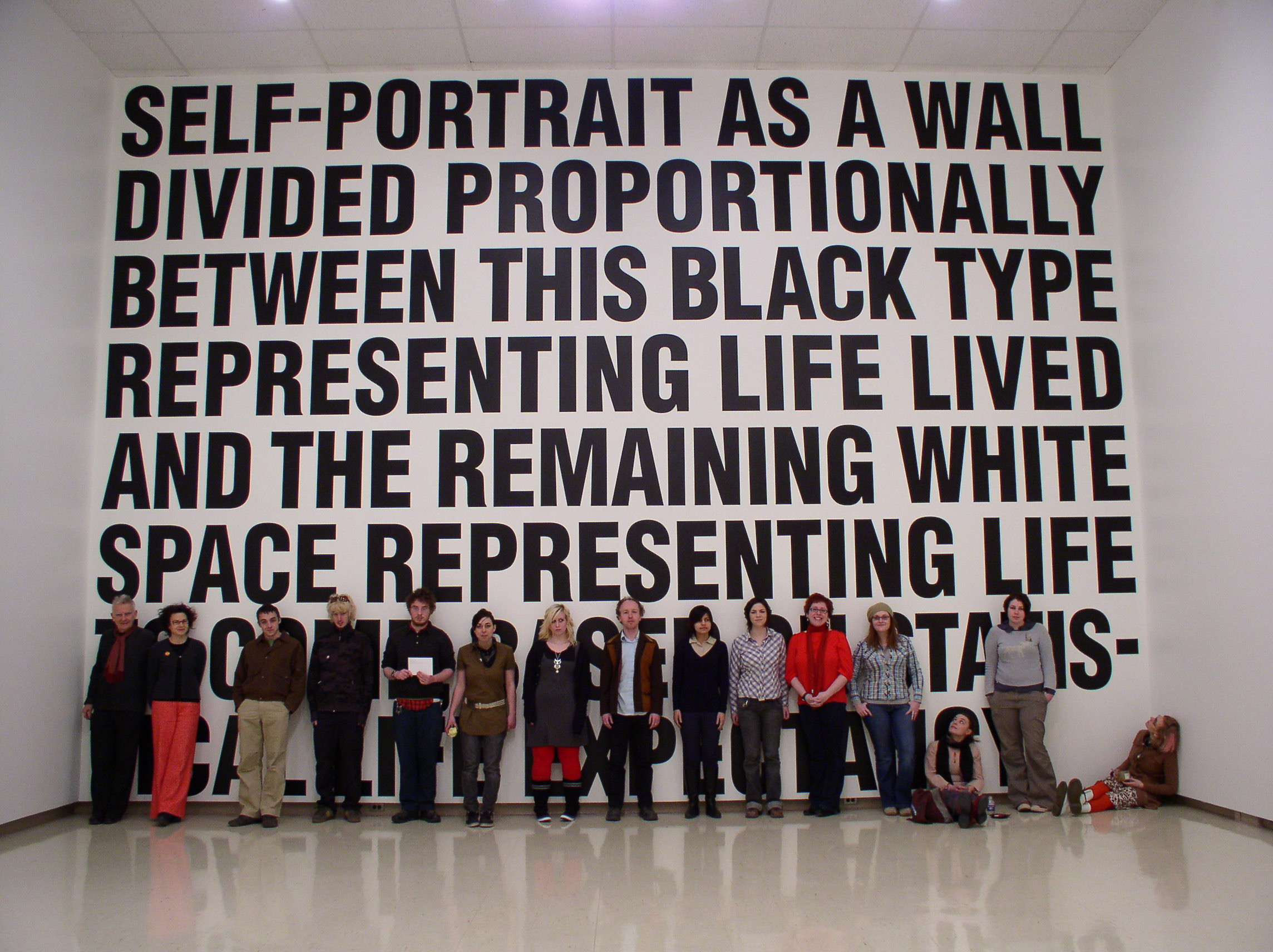 """In a large gallery space, a group of students line a wall. They are partially covering the last two lines of a text-based artwork that fills the wall from the floor to ceiling. The text set in bold, black capital letters and reads """"Self-portrait as a wall divided proportionally between this black type representing life lived and the remaining white space representing life to some based on statistical life expectancy."""""""