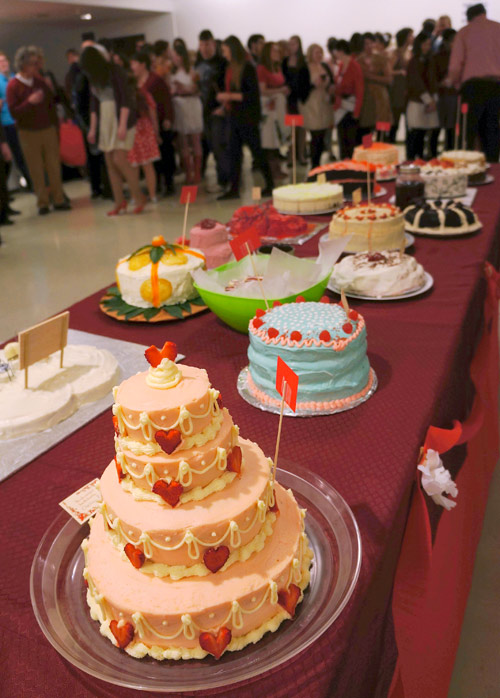 A long table displaying several elaborately decorated cakes on a red table cloth. A crowd of people of all ages mingle together in the gallery space behind the table.