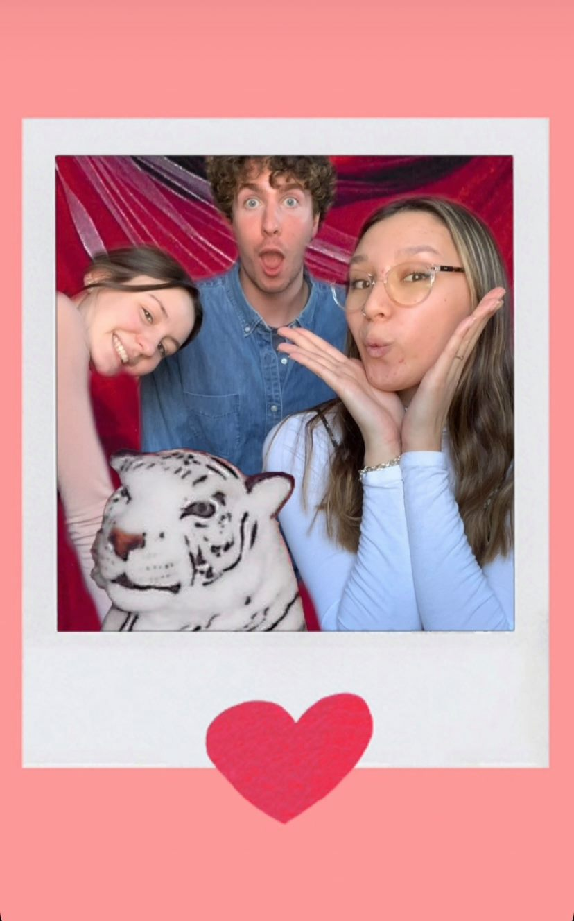 Three adults pose with a plush white tiger inside a polaroid frame.