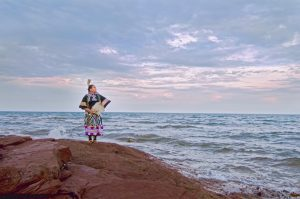 A figure dressed in a colourful jingle dress confidently stands on a large red-brown rock looking out over the ocean. They hold a fan made of feathers in front of their body and also wear feathers in their hair.