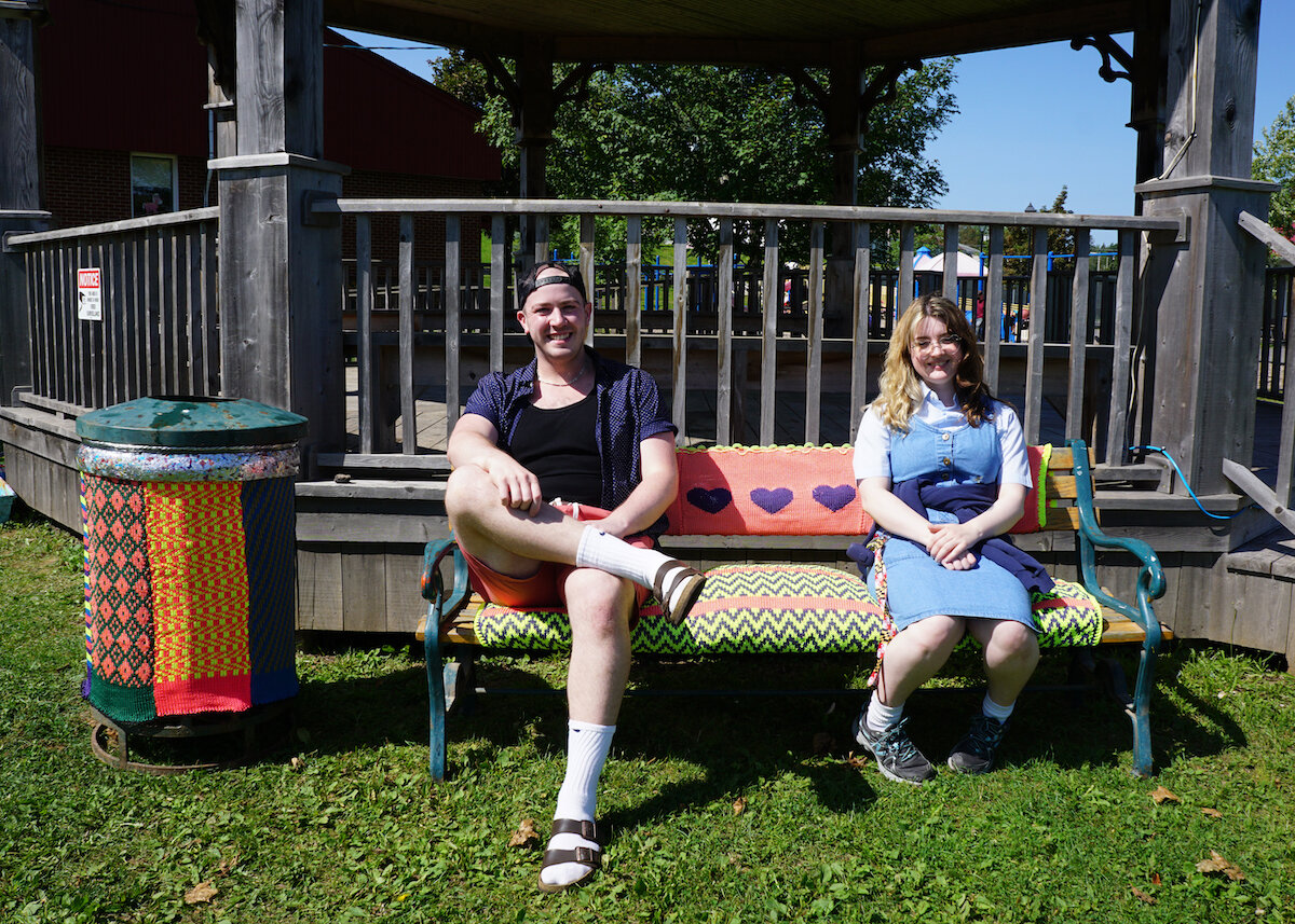 In a public park, two adults sit smiling on a bench decorated with bright colourful knitting. To their left, a garbage can is adorned with a knitted cover. The cover is made of several patterns and colours.
