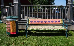 In a public park, a bench and garbage can are decorated with bright colourful knitting. The covers are made of several vibrant colours and playful patterns.