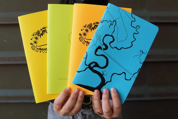 Two hands hold up four brightly coloured sketchbooks with various designs on their covers.