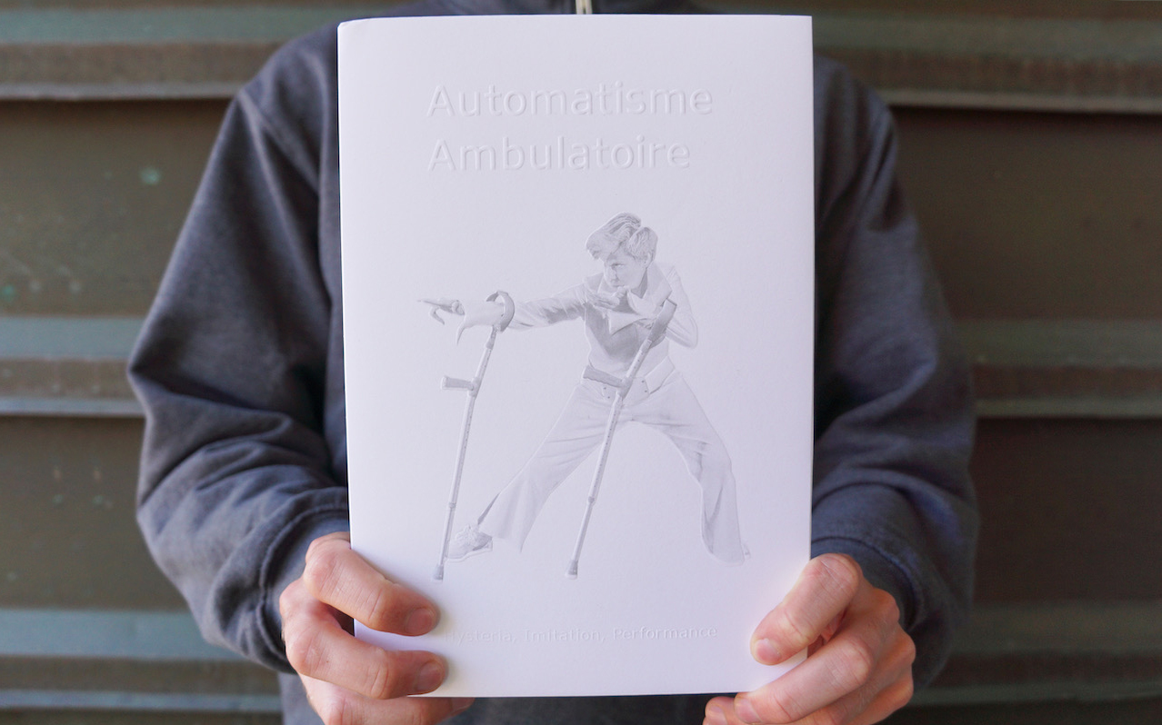 """Two hands hold a hardcover book with a matte white dust jacket. Below embossed text that reads :Automatisme Ambulatoire"""" is a photograph printed in light grey of Claire Cunningham striking a pose with her arm crutches. She is wearing a white jump suit with a wide belt and high collar."""