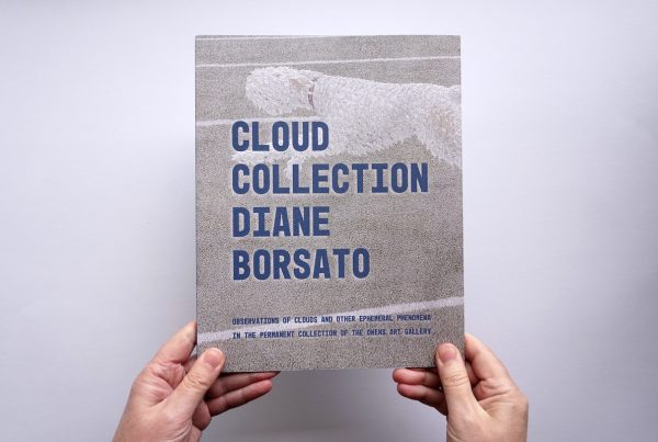 """Two hands hold the cover of a Cloud Collection with """"CLOUD COLLECTION DIANE BORSATO"""" in large uppercase blue type."""
