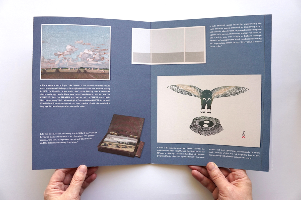 Two hands hold open a double-page spread of Cloud Collection showing images of artworks and texts.