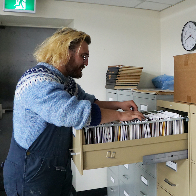 Jack Symmonds stands at a filing cabinet looking through many white file folders. He is wearing overalls, a wool sweater and glasses.