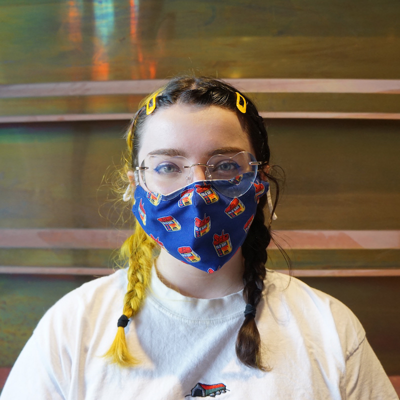 A portrait of Sophia, wearing a blue cloth mask and heart shaped glasses. Their hair, half yellow, half brown is braided.